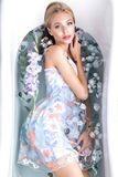 Beautiful girl in a summer dress in the bathroom with flowers. Beauty face. royalty free stock images