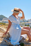 Beautiful girl in a summer dress and hat on the seashore near a background old city europe. Mediterranean Sea, Sitges Royalty Free Stock Photography