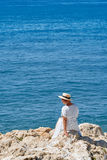 Beautiful girl in a summer dress and hat on the seashore near a background old city europe. Mediterranean Sea, Sitges Stock Photo
