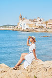 Beautiful girl in a summer dress and hat on the seashore near a background old city europe. Mediterranean Sea, Sitges Royalty Free Stock Photos