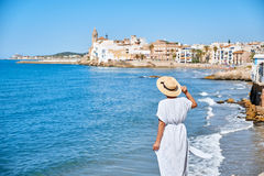 Beautiful girl in a summer dress and hat on the seashore near a background old city europe. Mediterranean Sea, Sitges Royalty Free Stock Image