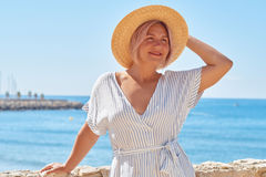 Beautiful girl in a summer dress and hat on the seashore near a background old city europe. Mediterranean Sea, Sitges Stock Photography