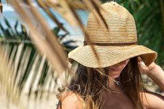 Beautiful girl in a summer hat on a background of palm leaves on stock photography
