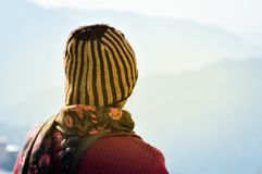 Beautiful girl in summer vacation in woolen hat in sunny day. Woman traveler looking at amazing mountain, Back view. Wanderlust royalty free stock photos