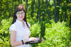 Beautiful girl in the summer woods with a laptop Royalty Free Stock Photo