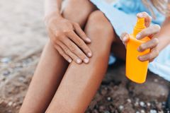 Beautiful girl, sun cream application, on the beach, feet close-up, jar of sun cream, isolated royalty free stock photo