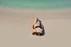 Beautiful girl sunbathes on a beach alone Royalty Free Stock Image