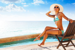Beautiful girl sunbathes while sitting on  chair Royalty Free Stock Photography