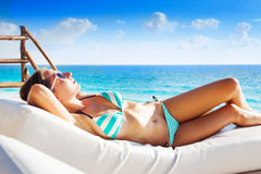 Beautiful girl sunbathes on white mattress alone Royalty Free Stock Image