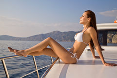 Beautiful girl sunbathing on a yacht. Beautiful girl traveling by yacht on the high seas Stock Photo