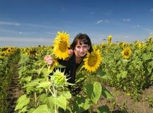 Beautiful girl between sunflower Royalty Free Stock Image