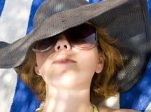 Beautiful girl in sunglasses. Lying on the beach Stock Photos