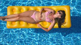 Beautiful girl in sunglasses and bikini lying on yellow inflatable mattress in swimming pool. Young tanned woman. Relaxing in basin of hotel on sunny day stock video