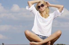 Beautiful girl in sunglasses on blue sky Stock Photo