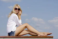 Beautiful girl in sunglasses on blue sky Royalty Free Stock Photo