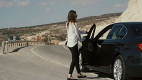 Beautiful girl in sunglasses catch a car on the road stock video footage