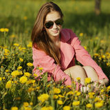 Beautiful girl with sunglasses in dandelion field Stock Photography