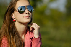 Beautiful girl with sunglasses in dandelion field Stock Image