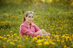Beautiful girl with sunglasses in dandelion field Stock Images