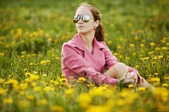 Beautiful girl with sunglasses in dandelion field Royalty Free Stock Photos