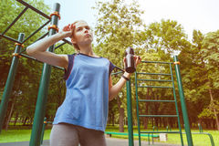 Beautiful girl in sunglasses drinks from white to-go cup holding skateboard on her shoulder at basketball court Royalty Free Stock Photography