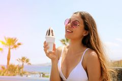 Beautiful girl with sunglasses eating ice cream on Tenerife beach in her travel holidays.  stock image