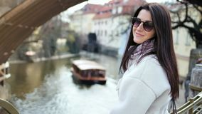 Beautiful girl in sunglasses enjoying walking on embankment in background ferry boat on water canal