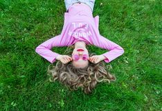 Beautiful girl in sunglasses lie on green grass. Top view stock photo