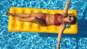 Beautiful girl in sunglasses and red bikini lying on yellow inflatable mattress in swimming pool. Young tanned woman stock video footage