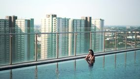 Beautiful girl in sunglasses in skyscrathcer pool stock video