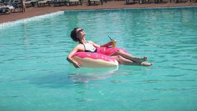 Beautiful girl in sunglasses sunbathing lying on an inflatable mattress donut. Young woman enjoys relaxing and bathes in stock footage