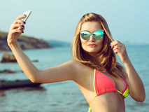 A beautiful girl in sunglasses and swimsuit is making selfie on the beach. royalty free stock photos
