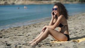 Beautiful girl in sunglasses talks on phone on the beach stock footage