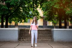 Beautiful girl in sunglasses walk by summer street with coffee. Lifestyle concept royalty free stock photo