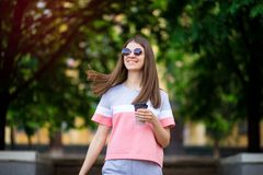 Beautiful girl in sunglasses walk by summer street with coffee. Lifestyle concept royalty free stock images