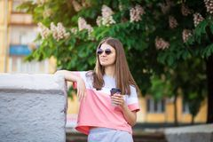 Beautiful girl in sunglasses walk by summer street with coffee. Lifestyle concept stock photos