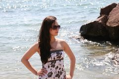 Beautiful girl in sunglasses by water Royalty Free Stock Photo