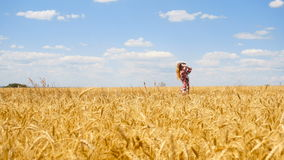 Beautiful girl on a sunny day goes into the wheat field. And straightens hair stock video footage