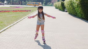 Beautiful girl on a sunny day, riding on roller skates. Girl in shorts and a striped T-shirt with a picture roller skates skating smiling stock video