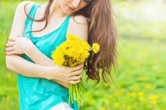 Beautiful girl in a Sunny summer day walking in the garden and keeps yellow dandelions in the hands. Beautiful girl in a Sunny summer day walking in the garden Stock Image