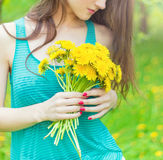 Beautiful girl in a Sunny summer day walking in the garden and keeps yellow dandelions in the hands Stock Photo
