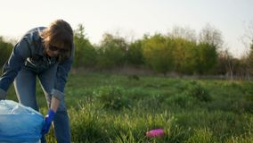 Beautiful girl at sunset collects trash in a large plastic bag. Ecological concept.  stock footage
