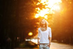 Beautiful girl in sunset light. Beautiful girl posing in autumn park on camera Royalty Free Stock Photo