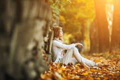 Beautiful girl in sunset light. Beautiful girl posing in autumn park on camera Royalty Free Stock Image