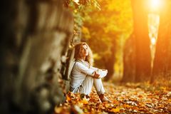 Beautiful girl in sunset light. Young beautiful girl sits on yellow leaves Royalty Free Stock Photography
