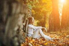 Beautiful girl in sunset light. Young girl sitting on a yellow sheet Stock Image