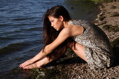 Beautiful girl  at sunset time. Beautiful girl  in a dress on the beach at sunset time Royalty Free Stock Photo