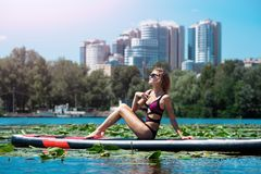 Beautiful girl on SUP board stock photo