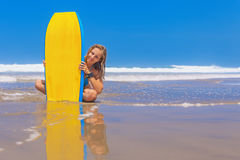Beautiful girl with surf board on sea beach with waves Stock Image