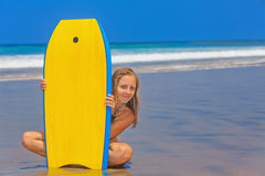 Beautiful girl with surf board on sea beach with waves. Happy girl - young surfer with bodyboard has fun on sea sand beach with waves. Family lifestyle, people Royalty Free Stock Images